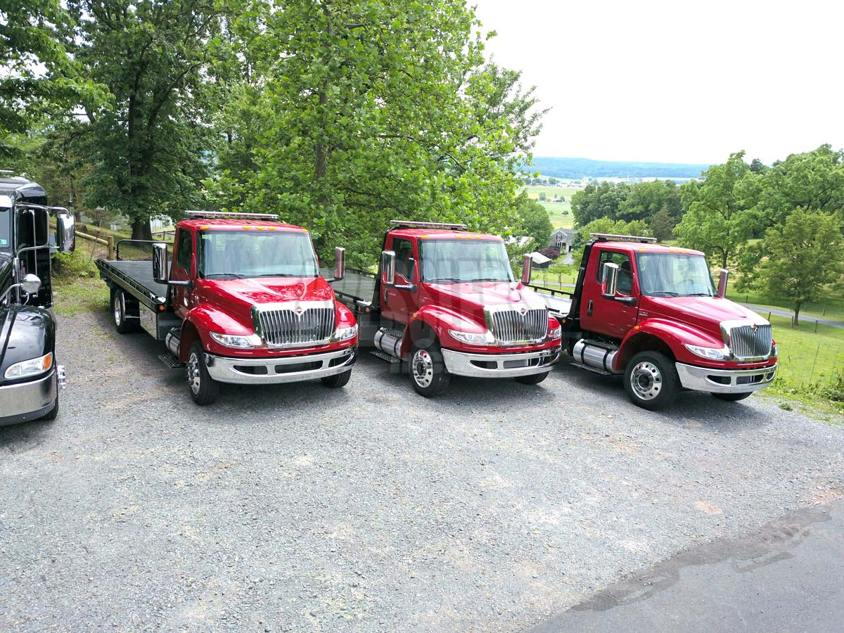 3 red Hino Century rollbacks - Steel